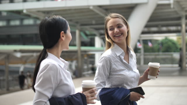 businesswoman walking with friend and talking together with coffee cup - partnership stock videos & royalty-free footage