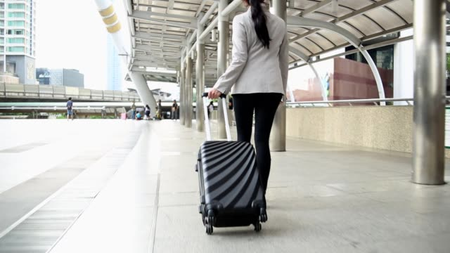 Businesswoman walking with suitcase and bag