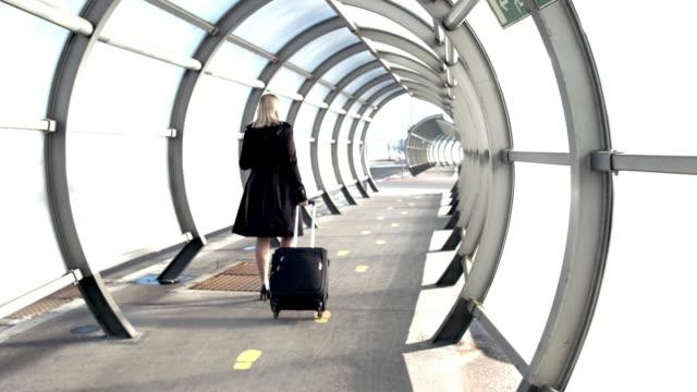 vidéos et rushes de femme d'affaires de ms marchant avec la valise dans le tunnel ensoleillé d'aéroport - plan en travelling