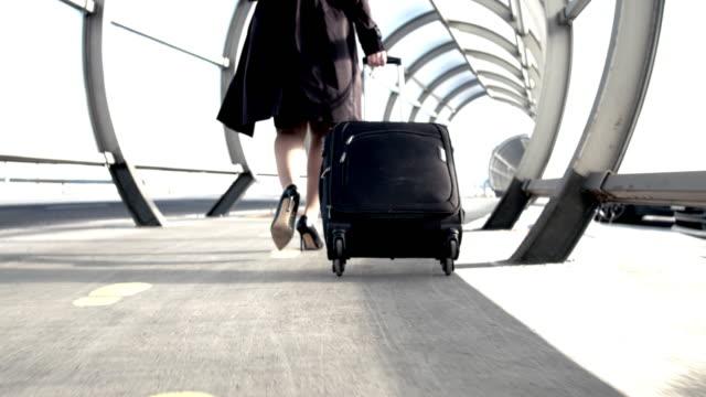 ms businesswoman zu fuß mit koffer in sonnigen flughafentunnel - geschäftsfrau stock-videos und b-roll-filmmaterial