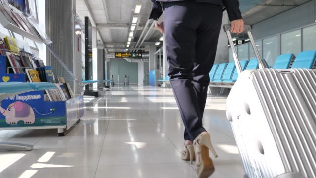 businesswoman walking with suitcase in the airport, business travel - bagaglio video stock e b–roll