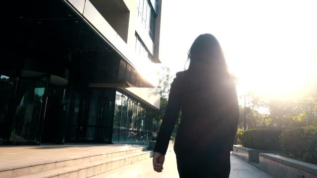 stockvideo's en b-roll-footage met zakenvrouw wandelen met zonlicht - rug