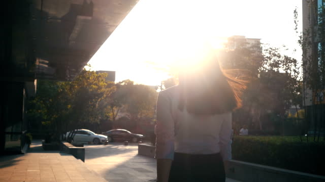 Businesswoman walking with sunlight