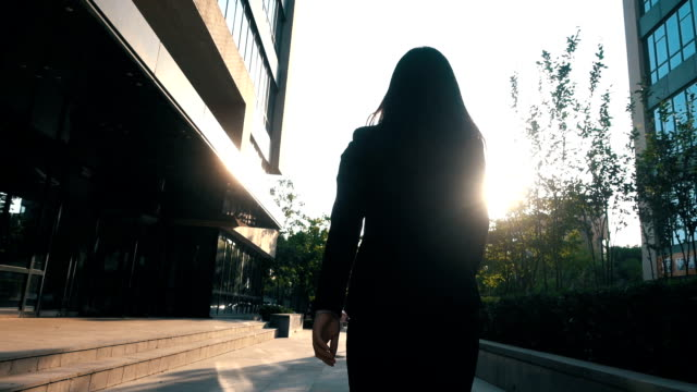 businesswoman walking with sunlight - businesswoman stock videos & royalty-free footage