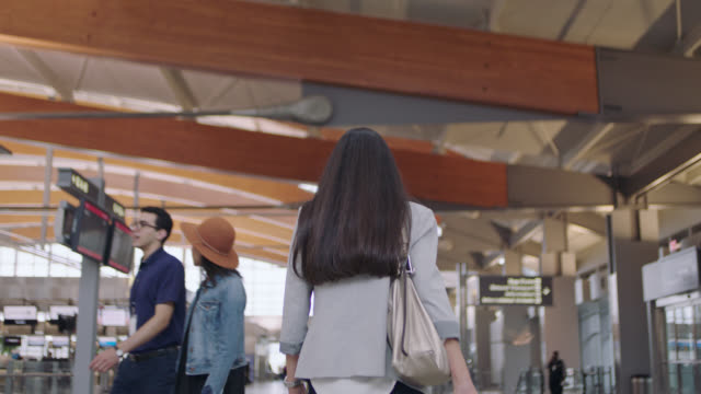 stockvideo's en b-roll-footage met businesswoman walks away towards ticket counter rolling suitcase behind her. - zakenreis