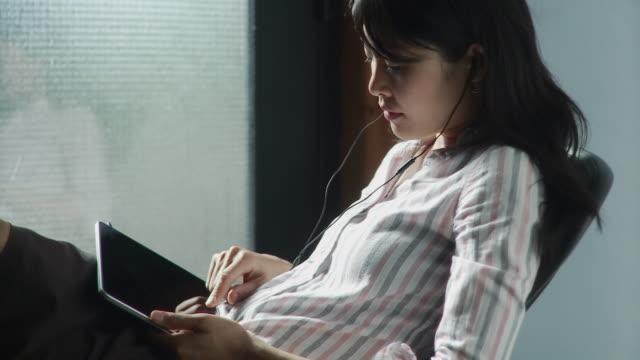 MS Businesswoman watching movie on digital tablet using headphones / Brooklyn, New York, USA