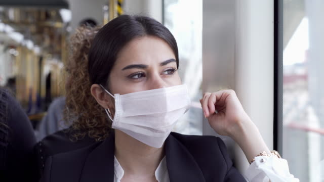 businesswoman wearing a mask while traveling - underground rail stock videos & royalty-free footage