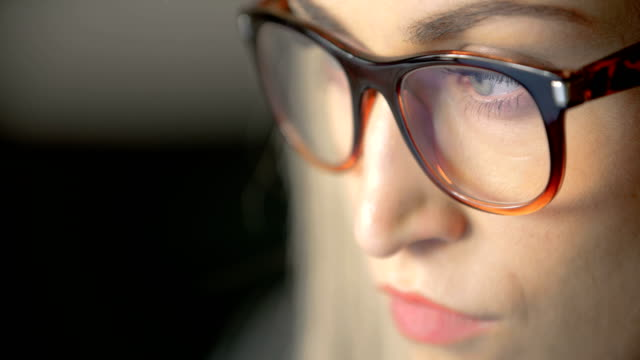 Businesswoman Wearing Eyeglasses While Using Laptop In Office