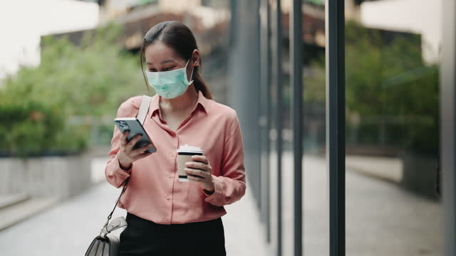 businesswoman wearing face mask hands typing message on mobile phone - phone message stock videos & royalty-free footage