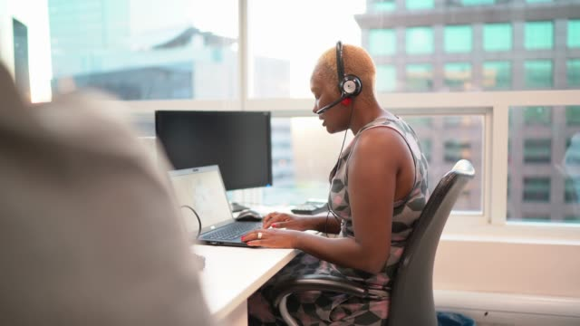 businesswoman wearing headset in office callcenter - estate agent stock videos & royalty-free footage
