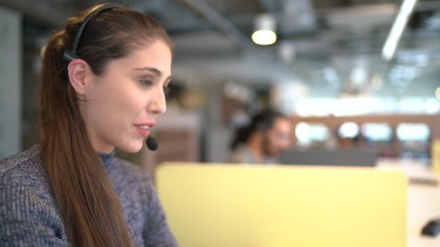 geschäftsfrau trägt headsets, während sie spricht und in modernen büro arbeitet - sekretärberuf stock-videos und b-roll-filmmaterial