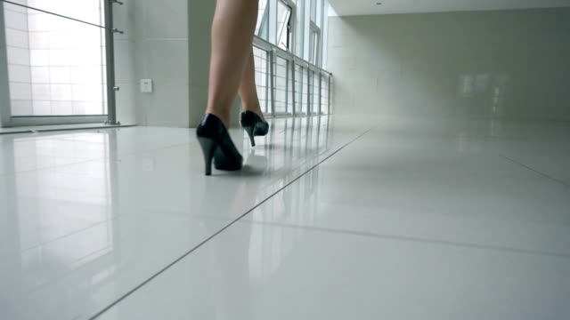 Businesswoman wearing heels walking in office corridor
