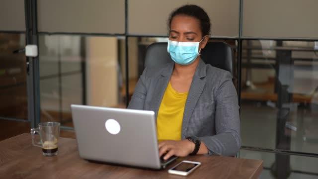 vidéos et rushes de femme d'affaires utilisant le masque protecteur dans le bureau pendant la pandémie de covid-19 - masque de chirurgien