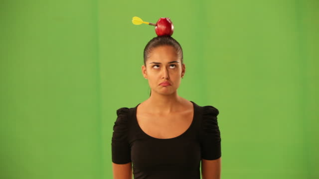 businesswoman with a apple sticked a dart on his head  - darts stock videos and b-roll footage