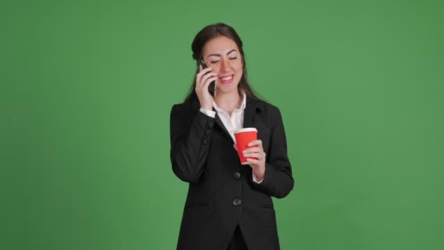 geschäftsfrau mit einem lächeln am telefon auf grünem hintergrund - weibliche angestellte stock-videos und b-roll-filmmaterial