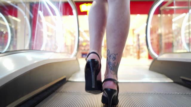 vídeos de stock, filmes e b-roll de empresária com tatuagem no tornozelo em salto alto subindo em máquina de escalada de escada - vestuário de trabalho formal