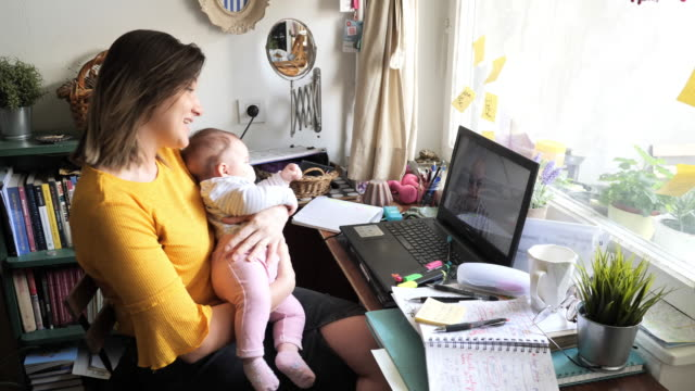 vídeos y material grabado en eventos de stock de empresaria con bebé en casa tener videollamada y teletrabajación - nueva realidad - evento virtual