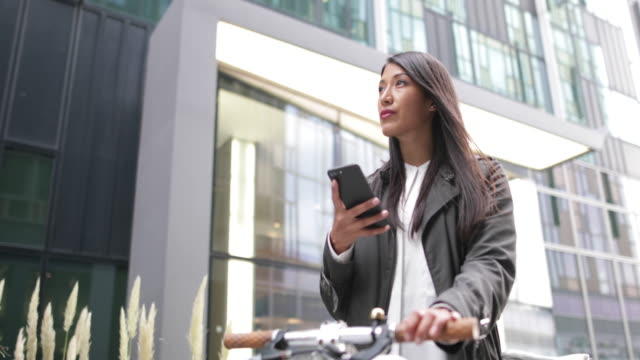 Businesswoman with bicycle and smartphone