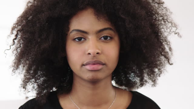 businesswoman with curly hair staring at camera - serious stock videos & royalty-free footage