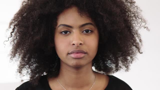 vídeos de stock, filmes e b-roll de mulher de negócios com cabelo curly que olha fixamente na câmera - trabalhadora de colarinho branco