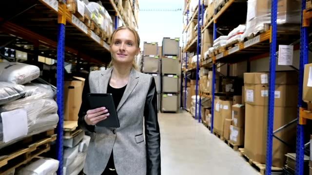 donna d'affari con dispositivo digitale in magazzino - mercanzia video stock e b–roll