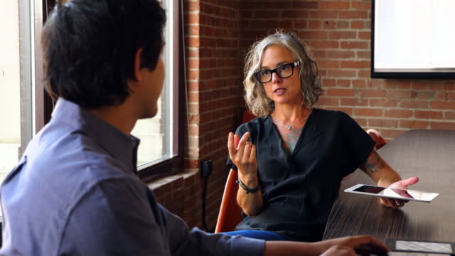 MS Businesswoman with digital tablet discussing project with coworker in office conference room