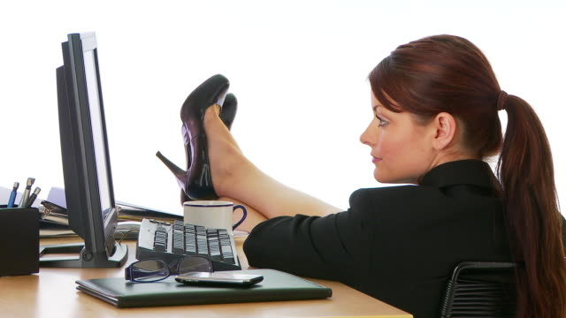 Businesswoman with feet up on desk