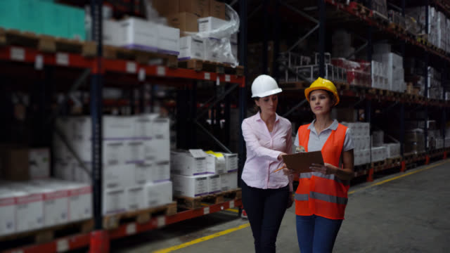 businesswoman with female warehouse supervisor looking at clipboard and different shelves at a distribution warehouse - world trade organisation stock videos & royalty-free footage