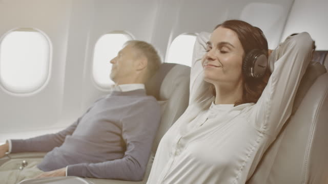 businesswoman with headphones relaxing in airplane - hands behind head stock videos & royalty-free footage