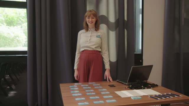 vídeos de stock e filmes b-roll de businesswoman with id cards in convention center - crachá etiqueta