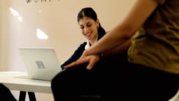 Businesswoman with laptop talking to coworkers