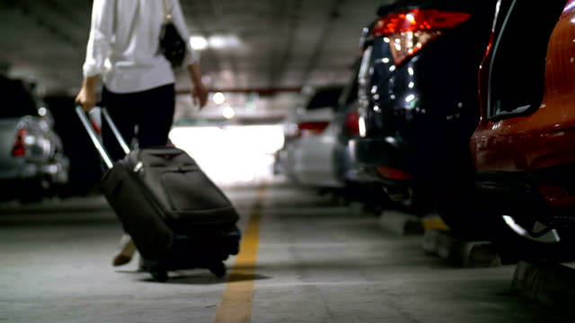 Businesswoman with luggage walking at car park