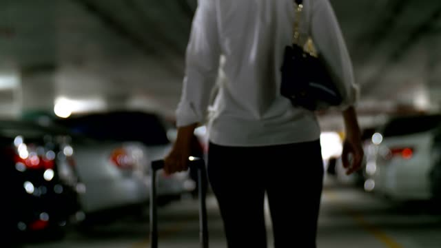 businesswoman with luggage walking at car park - parking stock videos & royalty-free footage
