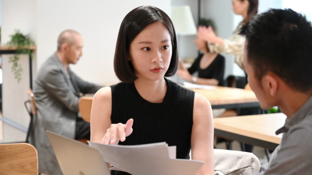 businesswoman with paperwork giving guidance to colleague - taiwan video stock e b–roll