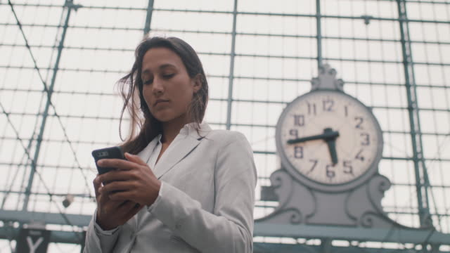 businesswoman with phone in front of big clock - formal stock videos & royalty-free footage