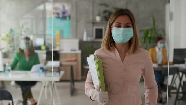 businesswoman with protective face mask in office - safety stock videos & royalty-free footage