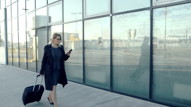 ms businesswoman with smart phone and suitcase walking on airport sidewalk - pulling stock videos & royalty-free footage