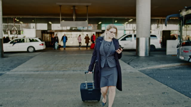 ms businesswoman with smart phone and suitcase walking outside airport - pulling stock videos & royalty-free footage