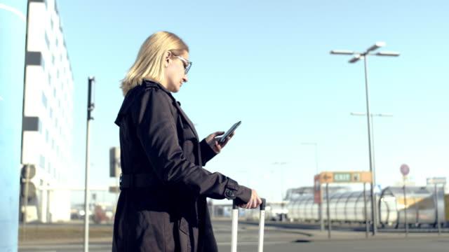 vidéos et rushes de femme d'affaires de ms avec le téléphone intelligent attendant le taxi crowdsourced sur le trottoir d'aéroport - valise