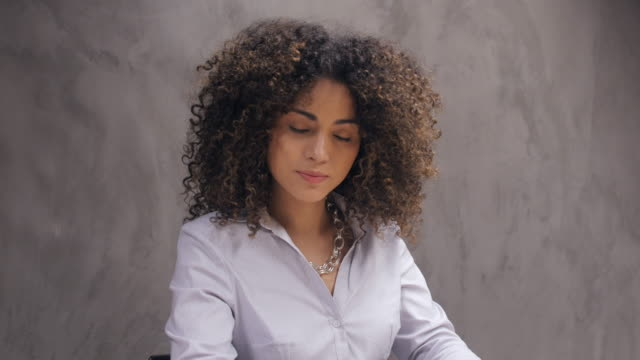 businesswoman working against gray wall in office - curly hair stock videos & royalty-free footage