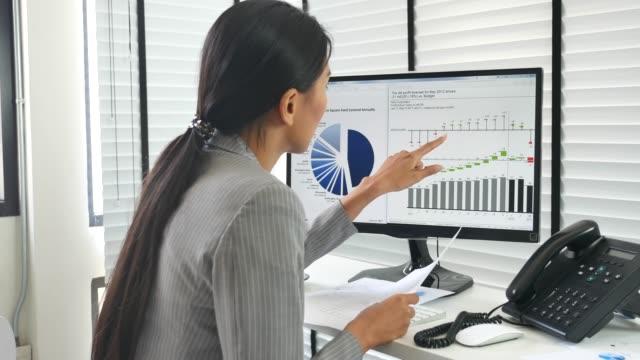 geschäftsfrau arbeitet bei der analyse von geschäftsdaten im büro - multitasking stock-videos und b-roll-filmmaterial