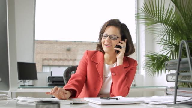 vídeos de stock e filmes b-roll de  ms businesswoman working and answering phone in office / new york, usa - caderno de notas