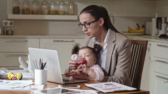 businesswoman working and giving water to baby - multitasking mum stock videos & royalty-free footage
