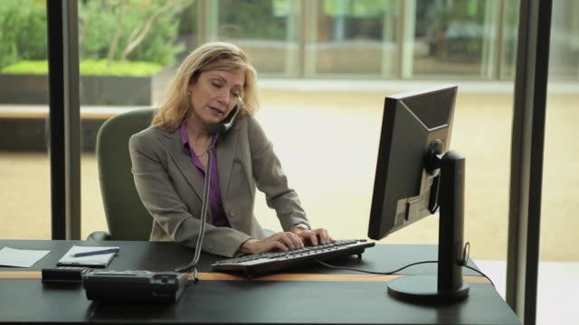vídeos de stock e filmes b-roll de ms pan businesswoman working at desk / portland, oregon, usa - caderno de notas