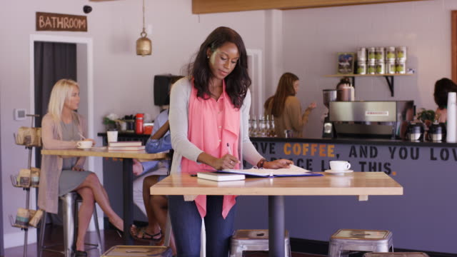 businesswoman working in a coffee shop - fatcamera stock videos & royalty-free footage