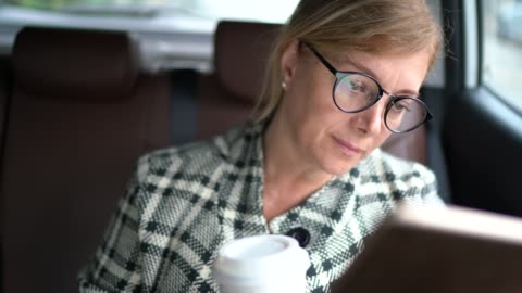 businesswoman working inside a cab, using digital tablet and drinking coffee - on the move stock videos & royalty-free footage