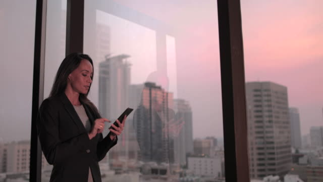 businesswoman working late using smartphone with city skyline in background - penthouse stock videos & royalty-free footage