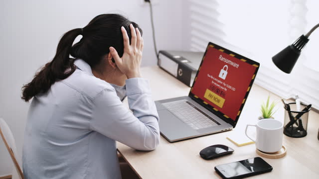 businesswoman working on a laptop waits for loading computer and finds out it is infected by a ransomware spyware virus - virus organism stock videos & royalty-free footage