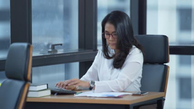 vidéos et rushes de femme d'affaires travaillant sur le bureau dans l'espace de bureau - tenue d'affaires formelle