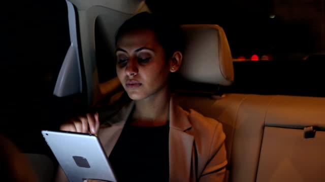 Businesswoman working on digital tablet in car, Delhi, India